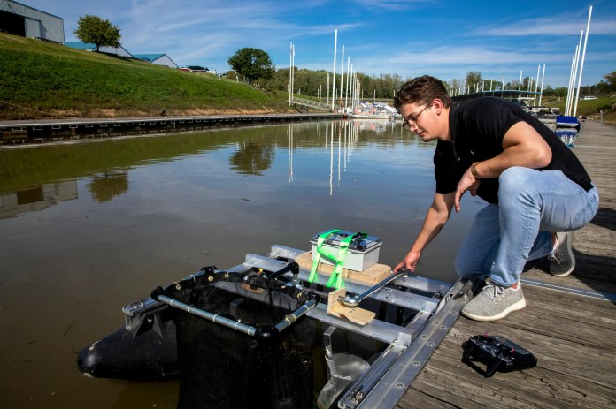 Michael Arens, CEO of Clean Earth Rovers, pulls the rover's trash collector basket out of the water during a test at Rivertowne Marina in the East End on Thursday, September 30, 2021. Clean Earth Rovers received support from University of Cincinnati's 1819 Hub and Venture Lab, including a $40,000 grant that helped create prototypes of the Plastics Piranha.