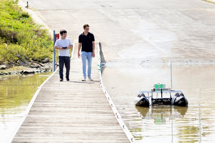 """Michael Arens, CEO of Clean Earth Rovers, and Xiahua Liu, vice president of autonomous systems, navigate the """"Plastics Piranha"""" around the Rivertowne Marina in the East End on Thursday, September 30, 2021. The rover vessels are 5 x 5-foot ships and can collect up to 300 pounds of waste per trip."""