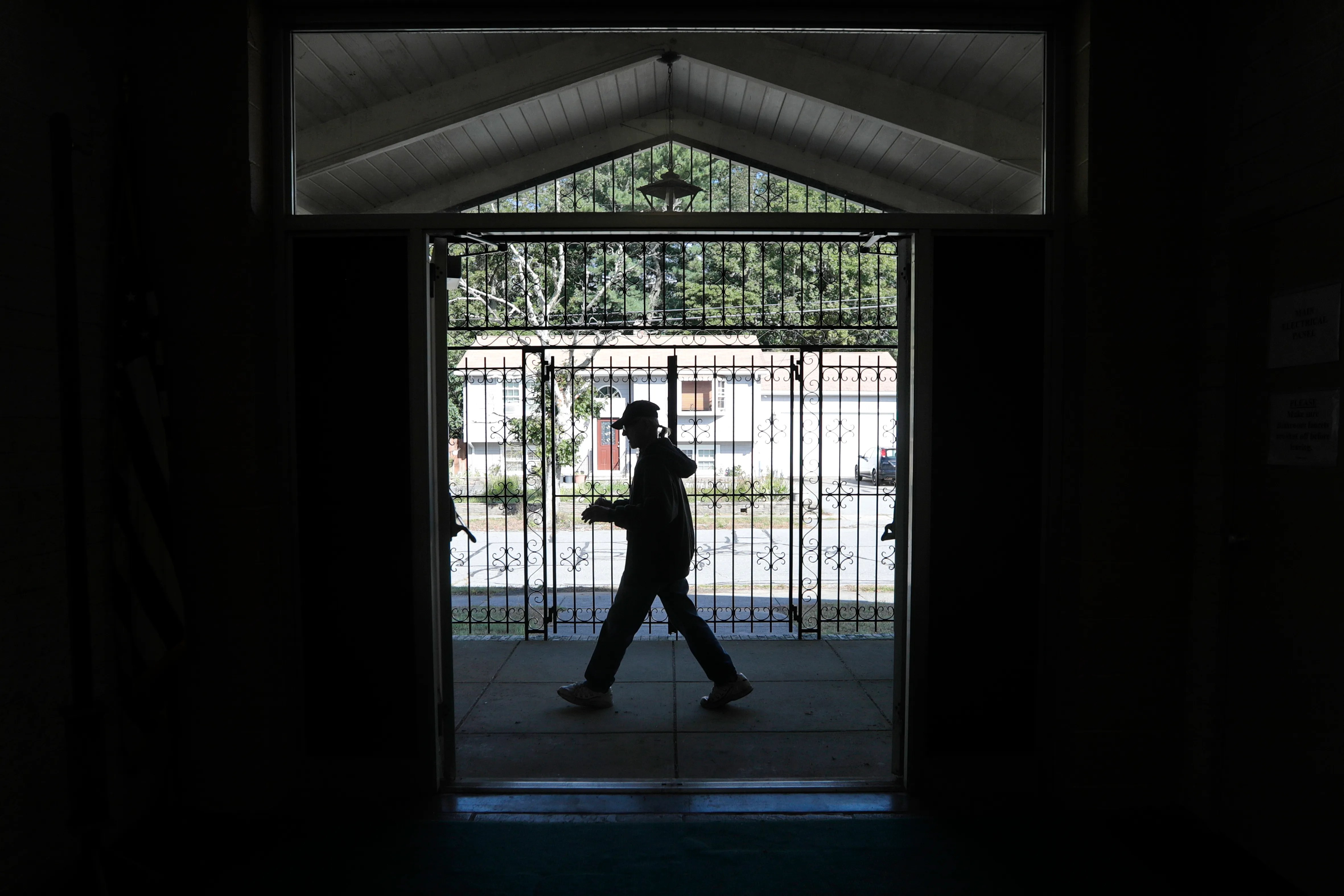 Richard Wisniewski walks past the closed gate at the Parish Center of Our Lady of Fatima Church on Acushnet Avenue in New Bedford, one of three churches closing this weekend.