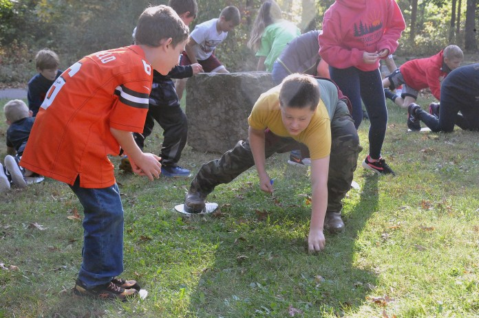 Zachary Johnson (left) and Justin Berger (right), as trees, try to pick up as many chips representing water, nutrients, sun and air to stay alive. This was a game created by one of the speakers to teach the students about all the things trees need to survive.