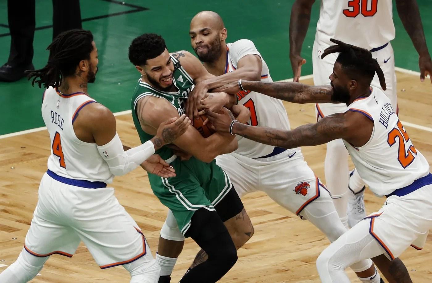Apr 7, 2021; Boston, Massachusetts, USA; Boston Celtics forward Jayson Tatum (0) battles for the ball with New York Knicks guard Derrick Rose (4), center Taj Gibson (67) and New York Knicks forward Reggie Bullock (25) during the second quarter at TD Garden.