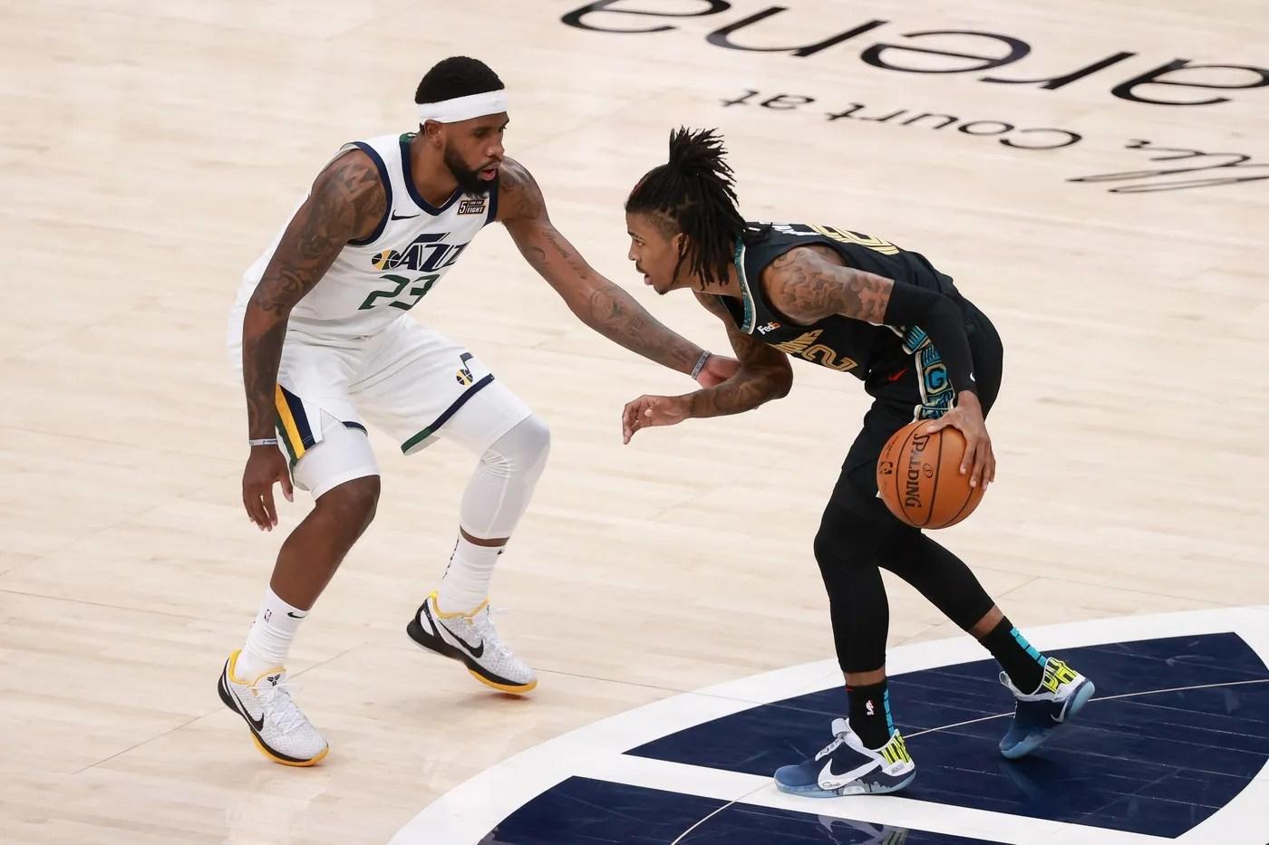 May 23, 2021; Salt Lake City, Utah, USA; Memphis Grizzlies guard Ja Morant (12) controls the ball against Utah Jazz forward Royce O'Neale (23) during the fourth quarter at Vivint Arena. Memphis Grizzlies won 112-109