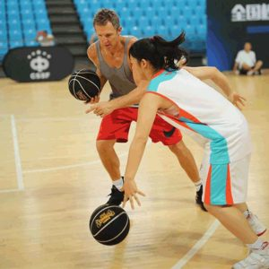 Ganon playing basketball with a teen girl during Live Training in China