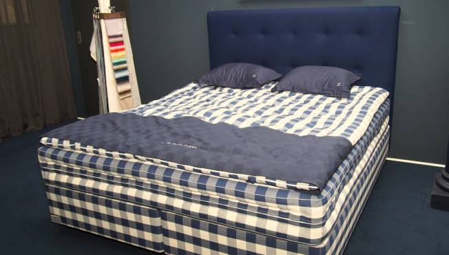 Ein Hästens Bett in blau weiß kariert