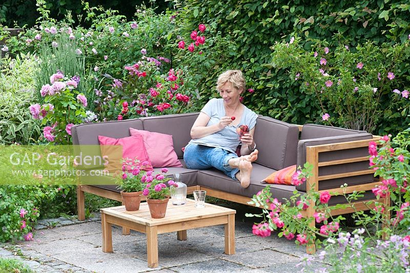Gap Gardens Woman Relaxing On Corner Sofa In Garden With A Small