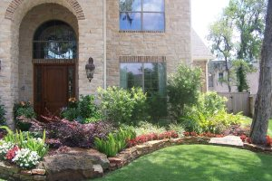 beautiful landscaping at a home with green plants, colorful flowers and a stacked stone border