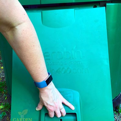 Hand grabbing the door on the composter and opening it up