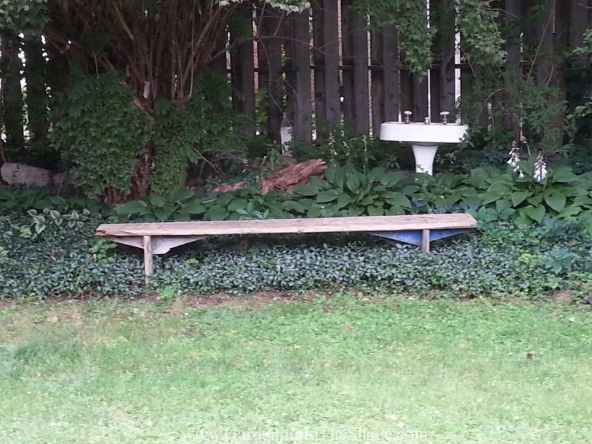 shady garden with old fashioned pedestal sink