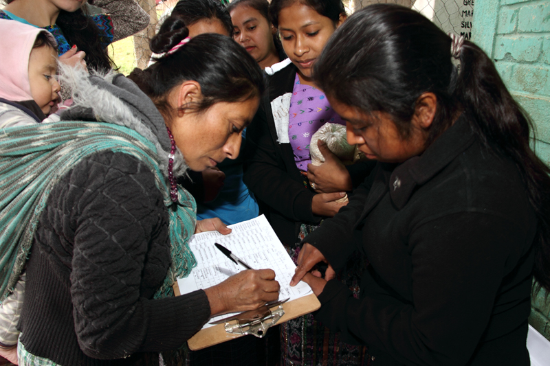 Young women distribute amaranth and vitamin supplements to mothers of chronically malnourished children.