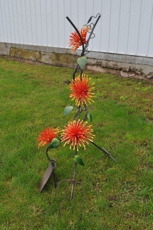 Shovel and pitchfork wrapped in orange flowers