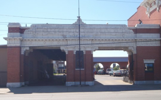 The front entrance gates to the original stockyards, also of brick construction, and terracotta and stone finishes, are located on the east side of the Exchange Building. Two gated bays flank a central enclosed bay, illuminated by one double-hung sash window, which would have been manned by a stockyard employee overseeing the flow of traffic, both human and livestock, in and out of the yards.