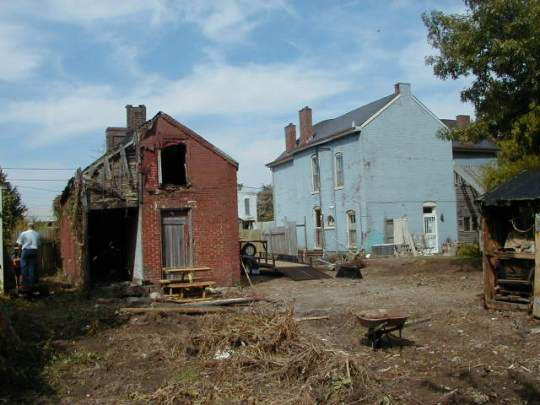 Looking toward the rear of the brick shotgun (on left) and the corner grocery store (on right) from the garden-in-waiting. Photograph provided by Jim McKeighen.