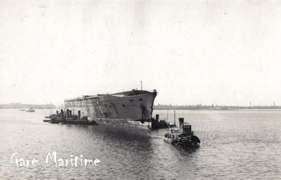 Tugs tow the Normandie to the scrapyard