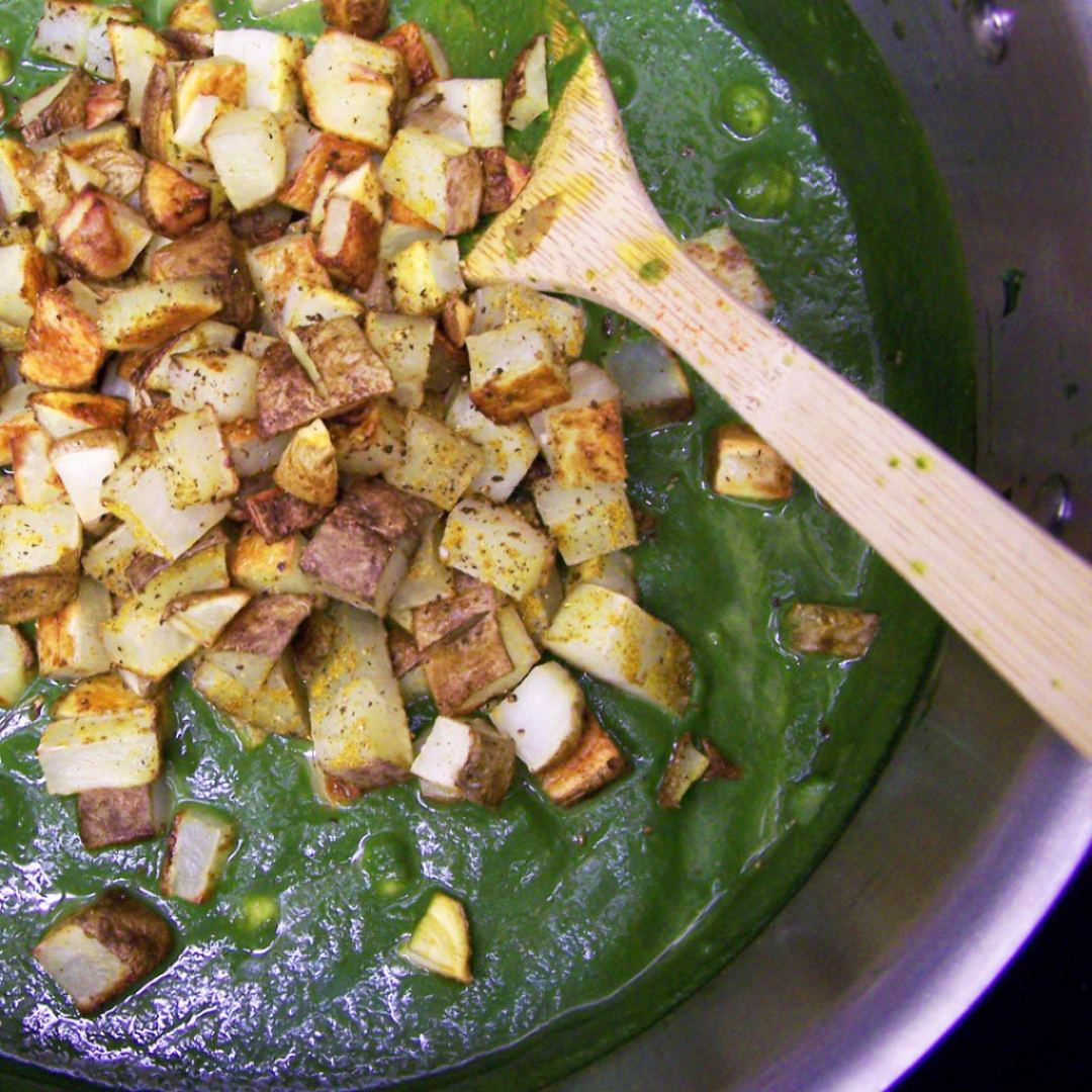 Potatoes added to spinach curry.