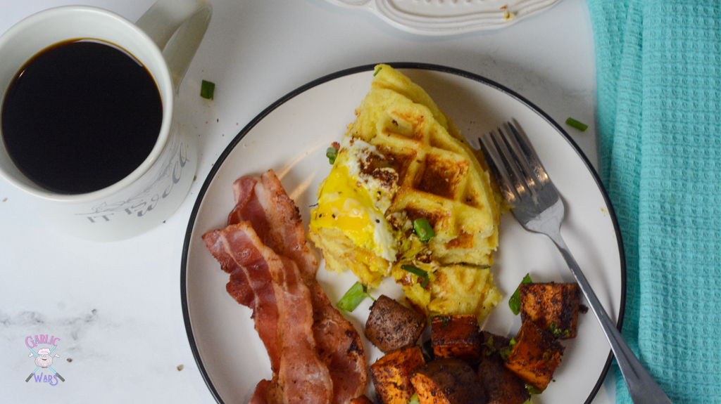An overhead picture of a breakfast plate with waffles, a fried egg, bacon, and sweet potato homefries with coffee on the side.