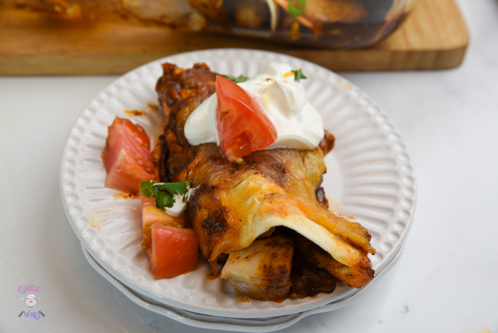 chicken enchilada on small white plate, topped with sour cream and tomatoes