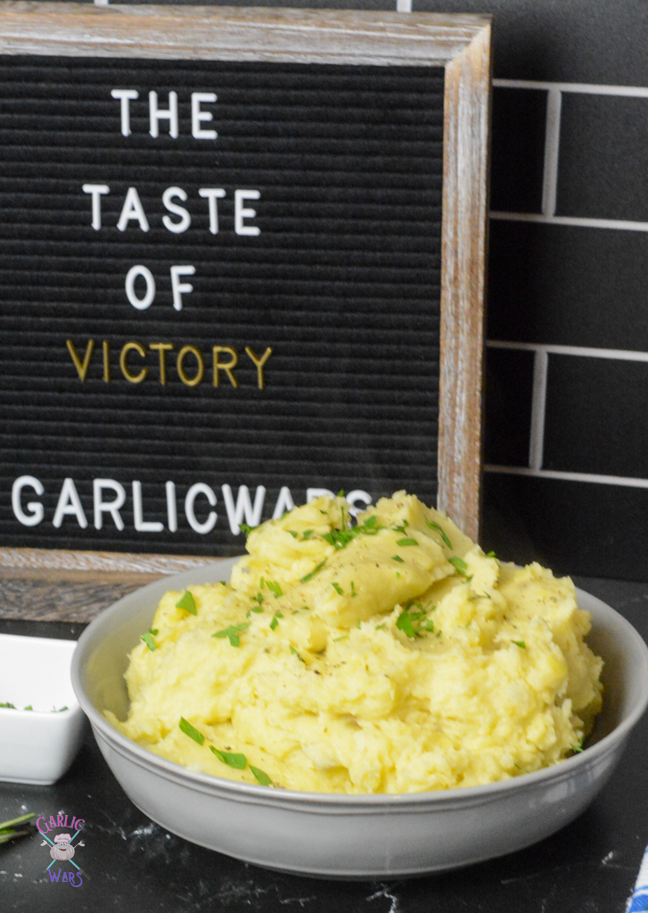 """A large grey bowl of mashed potatoes with a letterboard sign that reads """"the taste of victory"""""""