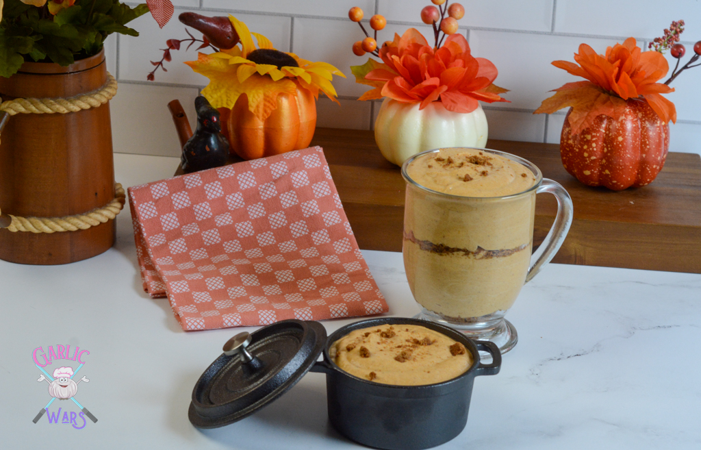 a large glass of pumpkin mousse with a small skillet of pumpkin mousse, with an autumn themed decor