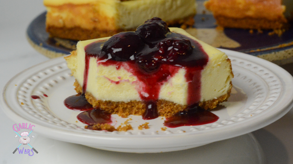 cheesecake bar on small white plate, topped with red wine sauce and whole berries