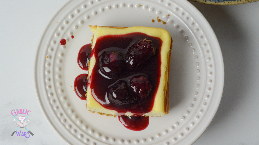 picture taken from above, cheesecake bar topped with red wine and berry sauce