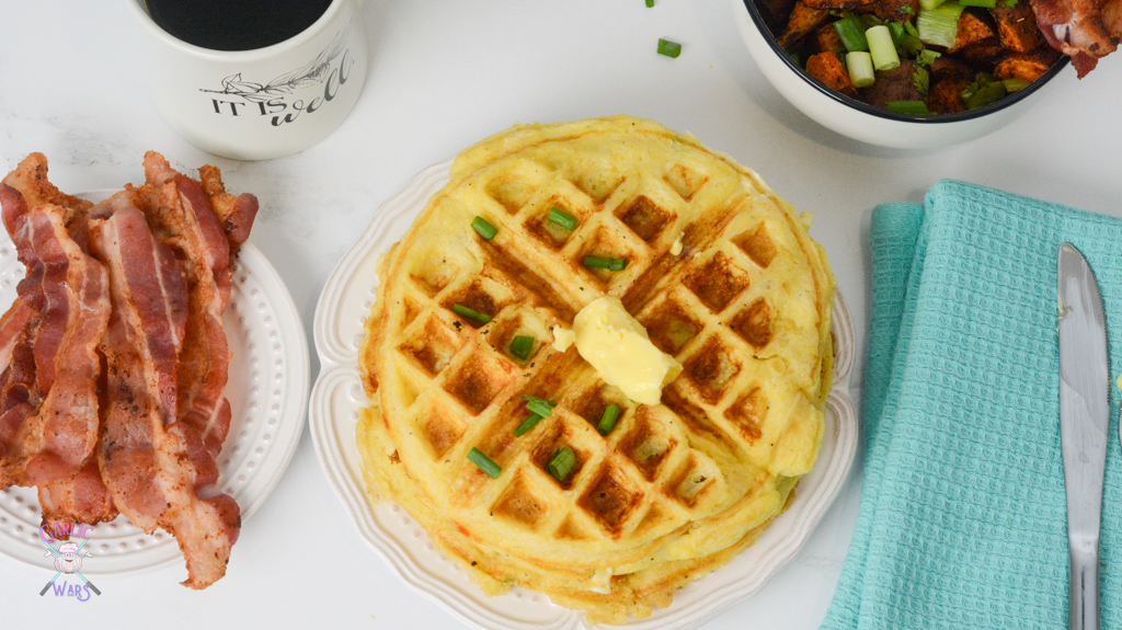 An overhead shot of waffles with some butter on top, and a side of bacon.