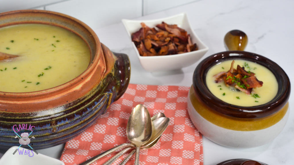 large crock of potato leek soup, with pink towel and four spoons, next to smaller crock of soup topped with bacon, with a dish full of bacon in the background.