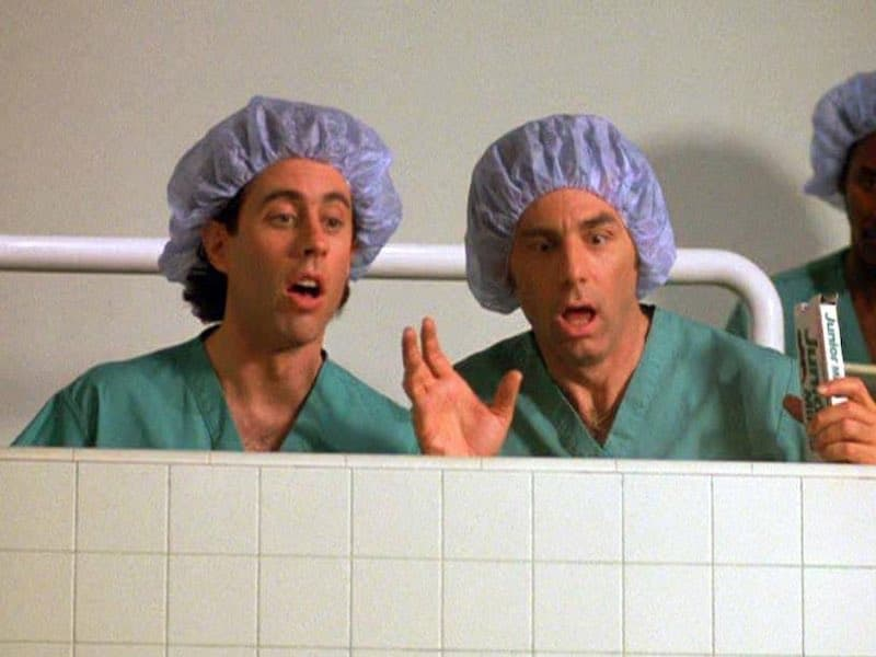 Jerry and Kramer in scrubs and hairnets, watching a Junior Mint fall into an open surgery.
