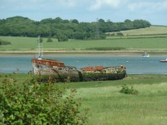 Rusting old boat on a river bank