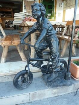 sculpture of a boy on a bike