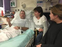 Two women visiting a man in hospital