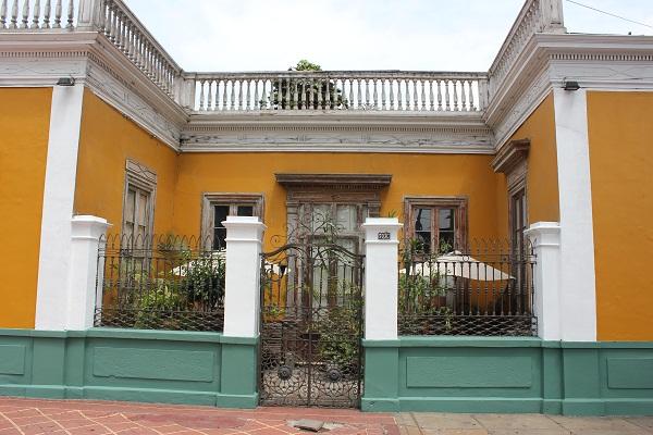Tolles Haus mit Betonpfosten und Metallzaun als Gartenzaun
