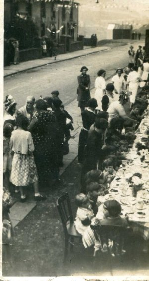 """Street Party, Bridgend Road 1937 or 38 The houses are now demolished, the end house was """"Joan's"""" a small grocers shop. The children are sat right in front of the school."""