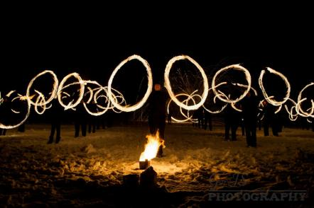 Performers swinging fire poi to the beating of drums