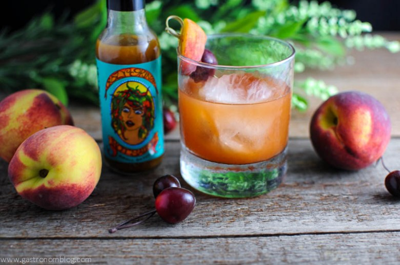 Fired Peach Old Fashioned in a rocks glass with hot sauce bottle with peaches in the background