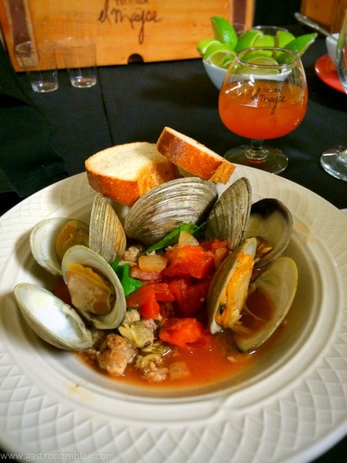 Clams in sauce with bread and tequila in glass behind