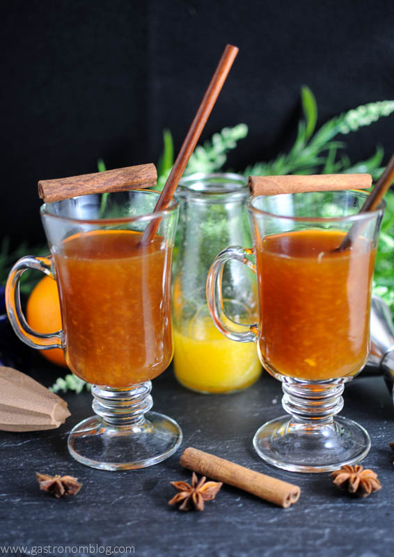 Tequila Hot Toddy Cocktail in two mugs with wooden spoons, cinnamon sticks and orange in the background