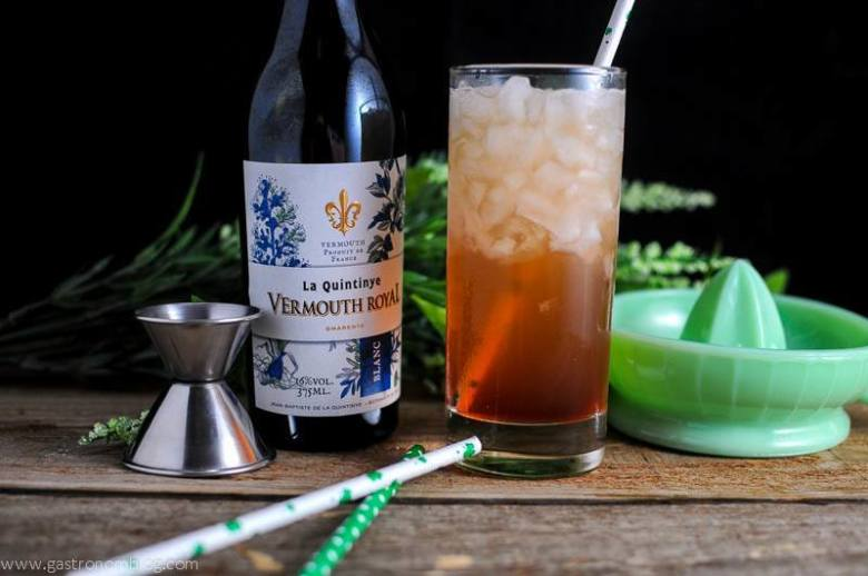 Irish Sour Cocktail in highball with clover leaf straws, jigger, juicer and white vermouth bottle