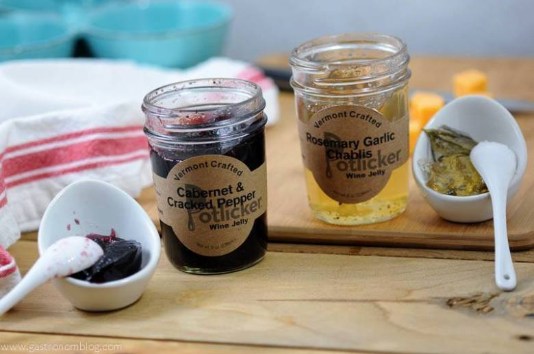 Cabernet and Chablis jams in jars with ceramic containers and spoons on a wood surface