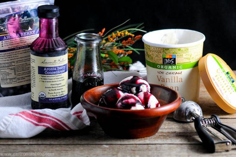 Aronia Berry Syrup on ice cream in wooden bowl. Aronia berry bottle and bag in background with ice cream container