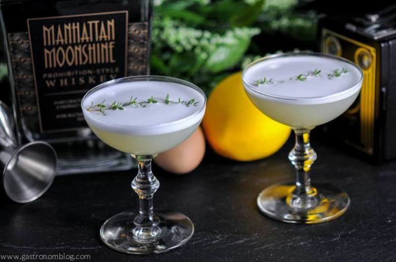 Thyme to Shine Cocktail in two cocktail coupes with egg, jigger, lemon and old camera in background with whiksey bottle