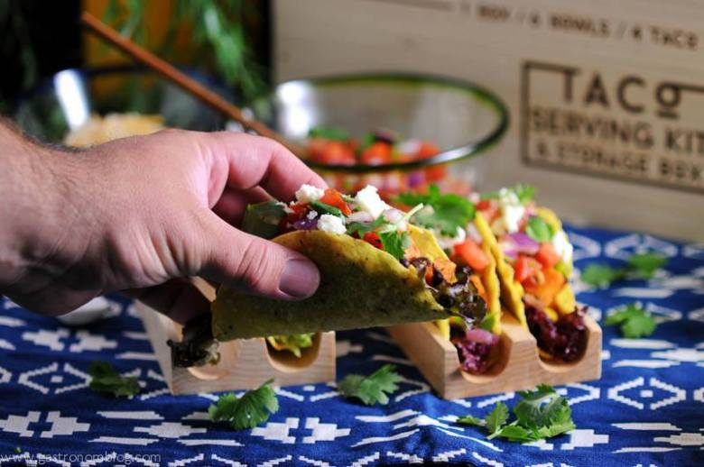 Sweet potato, black bean and corn tacos in wooden stands with glass bowls and wooden box in background
