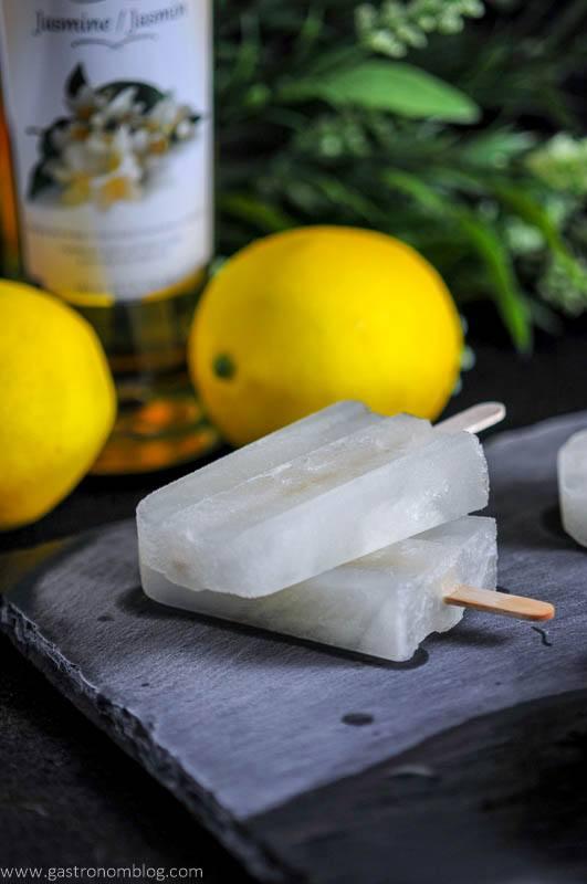 Jasmine Lemonade Gin Pop on a slate with lemons and simple syrup bottle