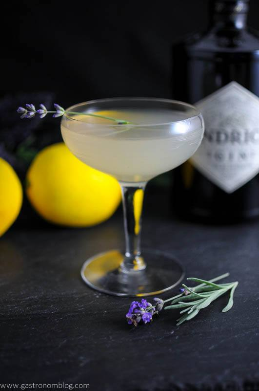 Lavender Bee's Knees Cocktail in coupe with lavender sprig. Lemon and flowers in background with gin bottle