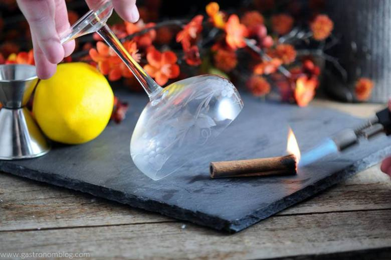 The Clove and Cider Cocktail being smoked with lit cinnamon. Flowers, lemon and jigger in background