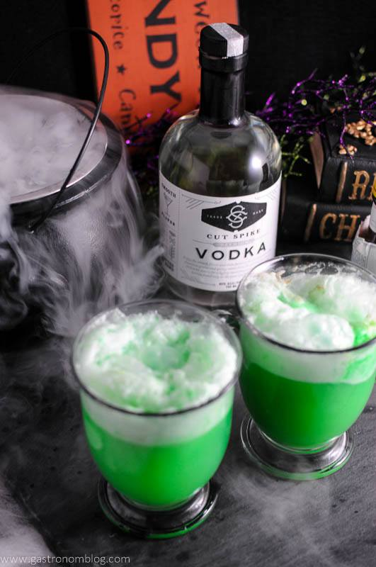 Polyjuice Potion cocktail in glass mugs, vodka bottle, books and dry ice in a cauldron