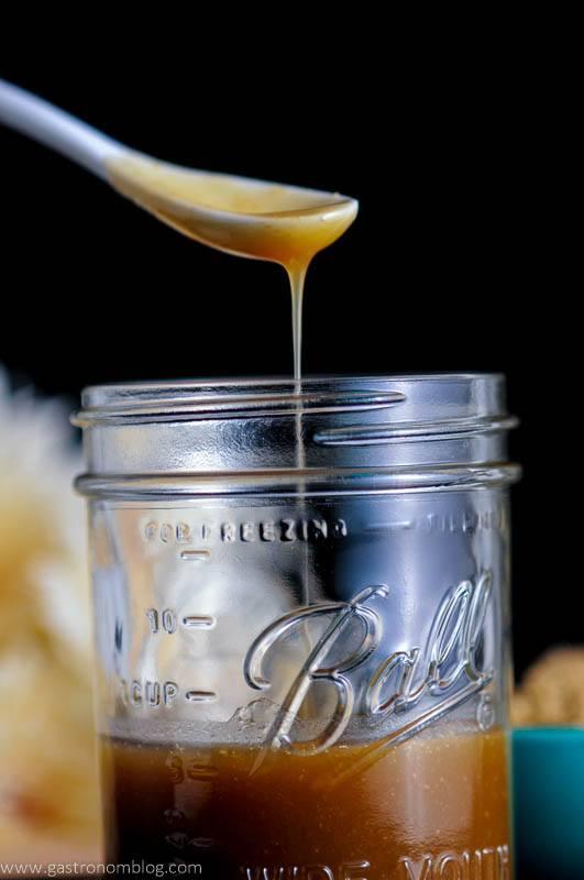 White ceramic spoon dripping Salted Bourbon Butterscotch Sauce into a mason jar