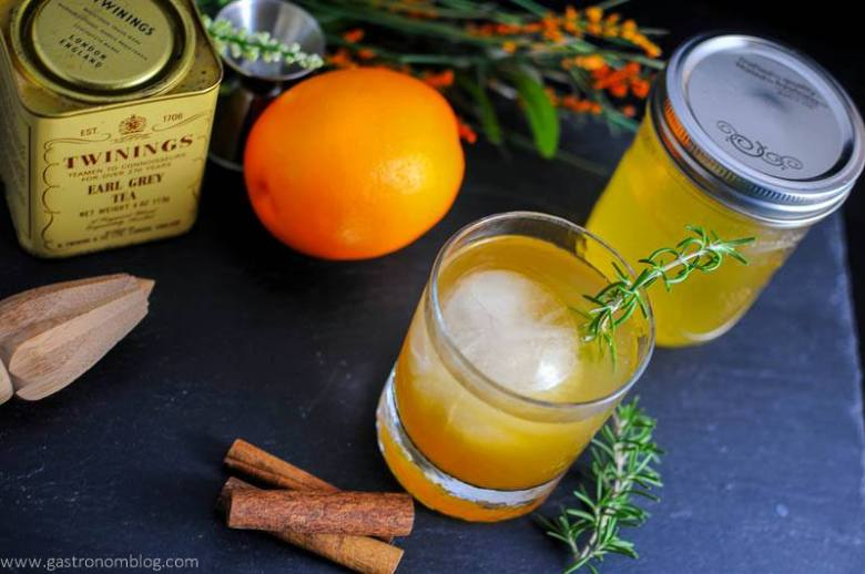Earl of Orange Cocktail with rosemary sprig and cinnamon sticks, Earl Gray tea tin, reamer, orange and mason jar