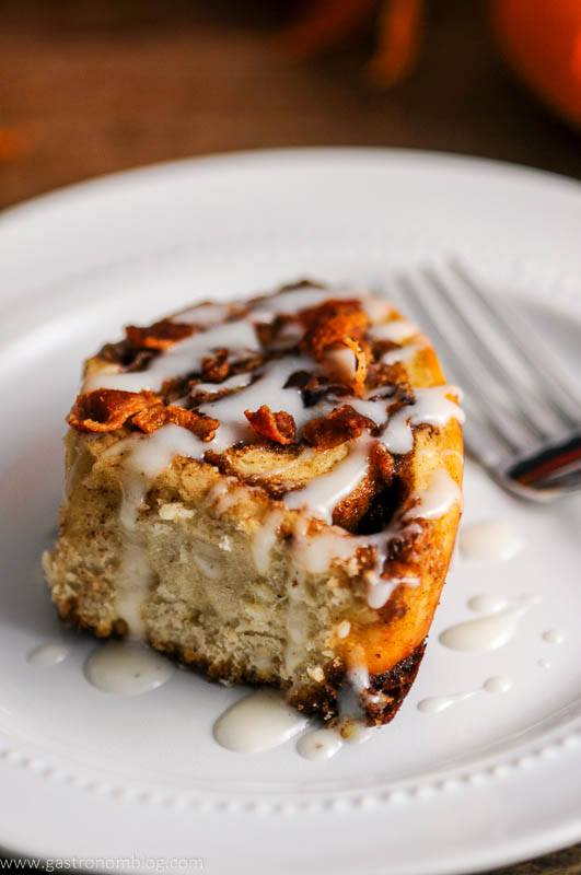 A fork sits next to bourbon bacon cinnamon rolls on a plate.