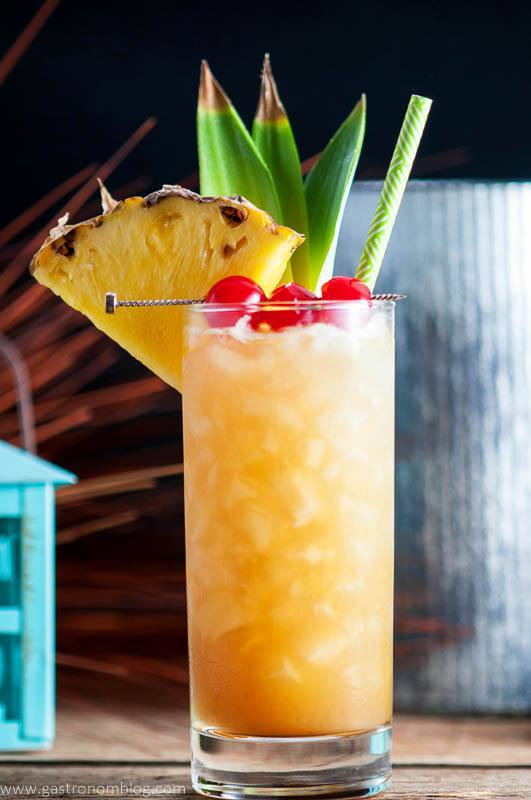 The Fall in Paradise cocktail in a tall highball glass with crushed ice and cherries and pineapple for garnish.