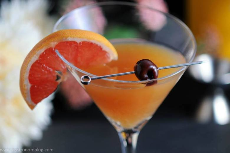 A martini glass with our apple cider sidecar cocktail, made with brandy, orange liqueur, lemon and bitters. Garnished with grapefruit and a brandied cherry.
